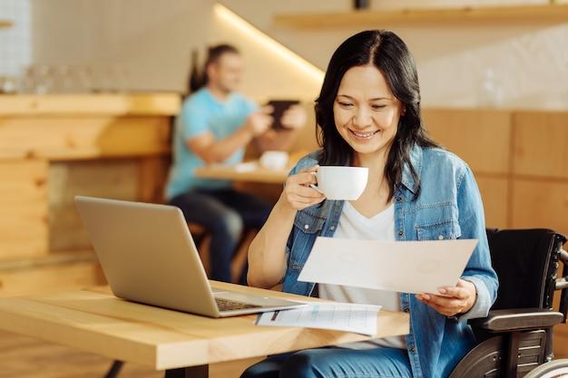 Linda mulher com deficiência, de cabelos escuros, sentada em uma cadeira de rodas, lendo um documento e bebendo café