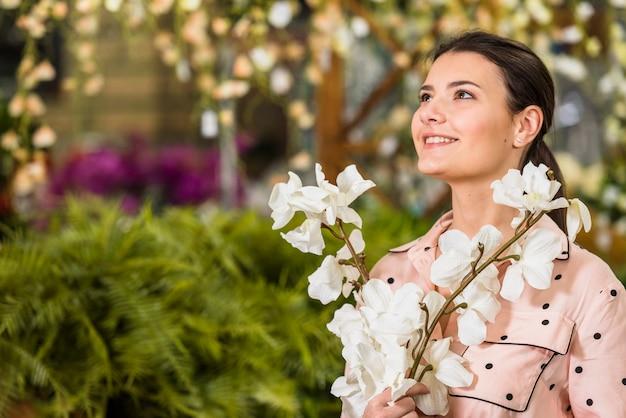 Linda mulher com flores brancas nas mãos
