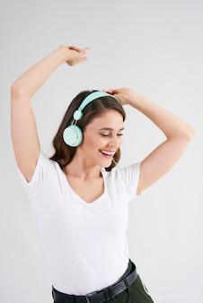 Linda mulher com fones de ouvido, ouvindo música e dançando