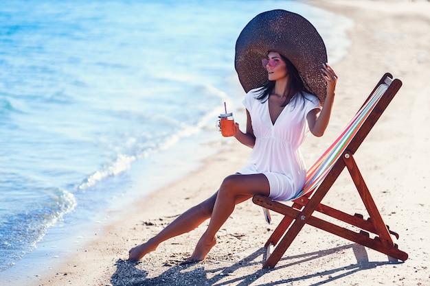 Linda mulher com grande chapéu de palha relaxando em uma espreguiçadeira de praia e bebe suco refrescante de férias de verão ...