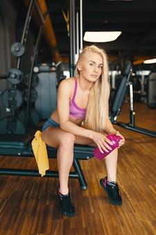 Linda mulher com longos cabelos loiros relaxantes no ginásio com uma garrafa de água-de-rosa