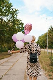 Linda mulher com mochila andando feliz com balões cor de rosa no parque. liberdade e conceito de mulheres saudáveis.