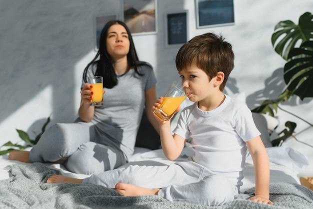 Linda mulher com o filho bebendo suco pela manhã na cama
