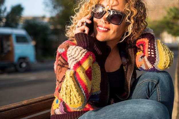 Linda mulher com óculos de sol ligando e conversando com a amiga ou namorado com a van azul no fundo