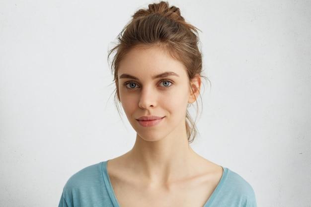Linda mulher com olhos azuis vivos, lábios bem formados e pele pura com coque de cabelo vestindo um suéter casual azul com aparência satisfeita. jovem sensual com rosto atraente olhando