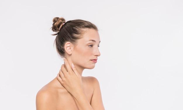 Linda mulher com ombros nus tocando o pescoço