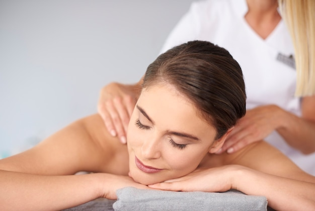 Linda mulher com os olhos fechados durante a massagem nas costas
