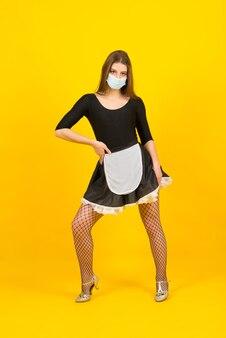 Linda mulher com roupas de empregada, posando com uma máscara protetora cobiçosa