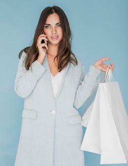 Linda mulher com sacos de compras, falando ao telefone