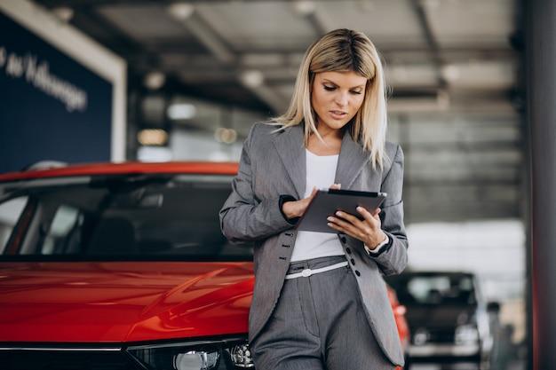 Linda mulher com tablet no carro showroom