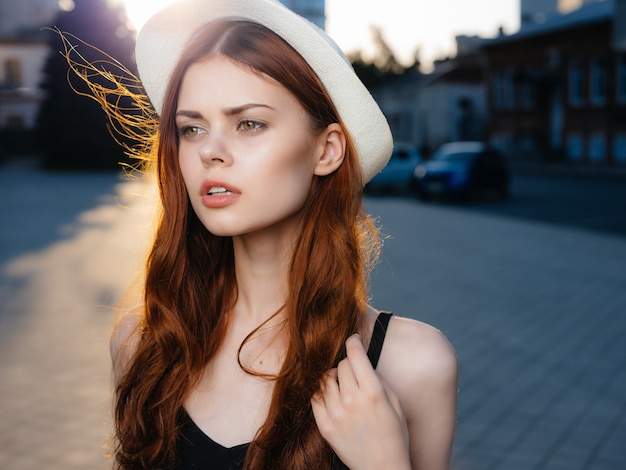 Linda mulher com um chapéu ao ar livre, posando de verão