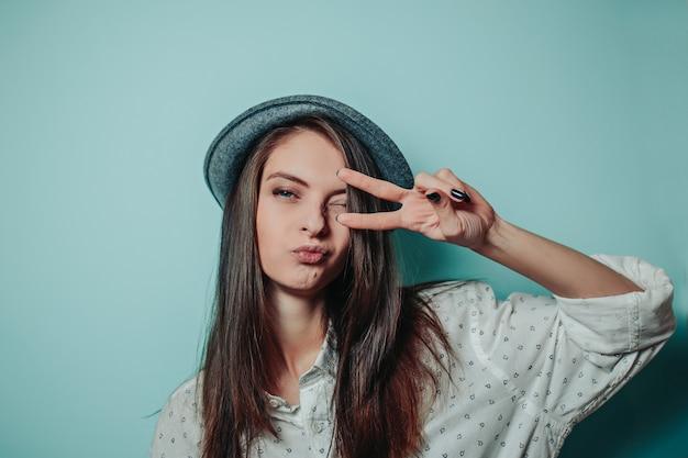 Linda mulher com um chapéu cinza com cabelos longos e camisa branca. mulher mostra sinal de paz com os dedos.