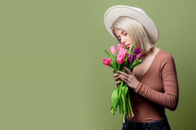 Linda mulher com um chapéu com buquê de tulipas