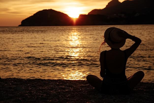 Linda mulher com um chapéu perto do mar