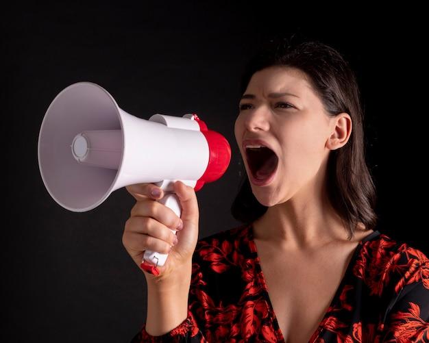 Linda mulher com um megafone gritando, espaço preto
