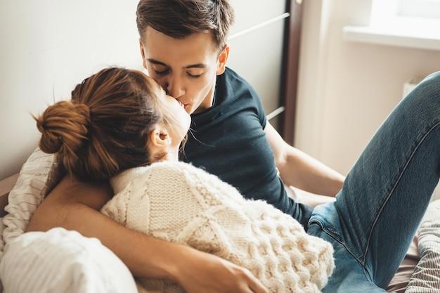 Linda mulher com um suéter de tricô branco beijando o marido enquanto estava deitada na cama