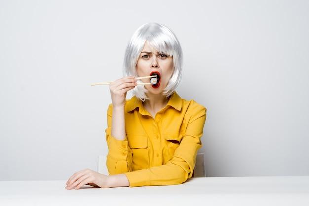 Linda mulher com uma peruca branca se senta em uma mesa com uma camisa amarela, rolos de sushi fazem um lanche.