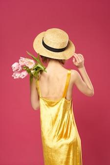 Linda mulher com vestido amarelo chapéu buquê de flores fundo rosa vista traseira