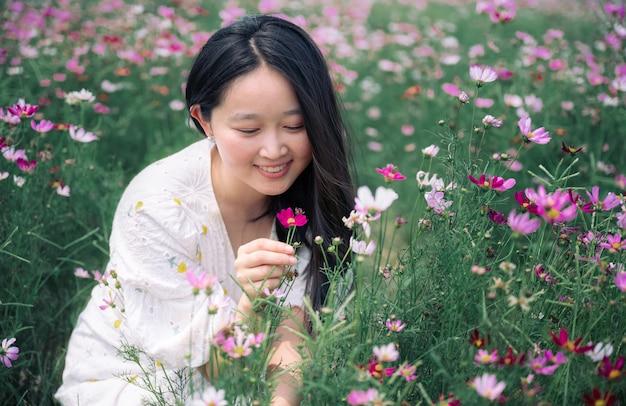 Linda mulher com vestido branco no jardim de flores