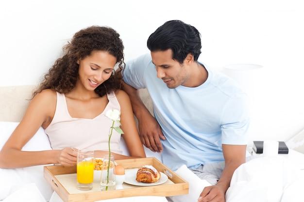 Linda mulher comendo cereais para o café da manhã deitado na cama