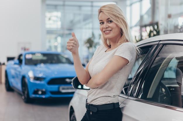 Linda mulher comprando carro novo, sorrindo alegremente.