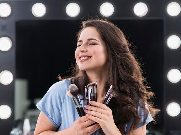 Linda mulher contente estilista de maquiagem com pincéis nas mãos