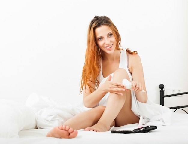 Linda mulher cuidando de pernas com creme cosmético