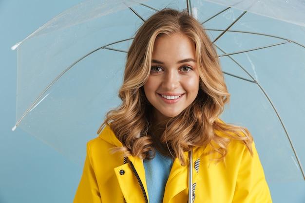 Linda mulher de 20 anos com capa de chuva amarela sob um guarda-chuva transparente