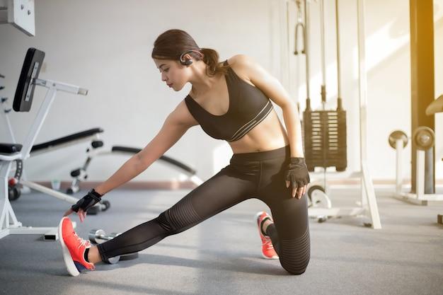 Linda mulher de ajuste muscular, exercitando os músculos do edifício e fitness mulher fazendo exercícios no gy