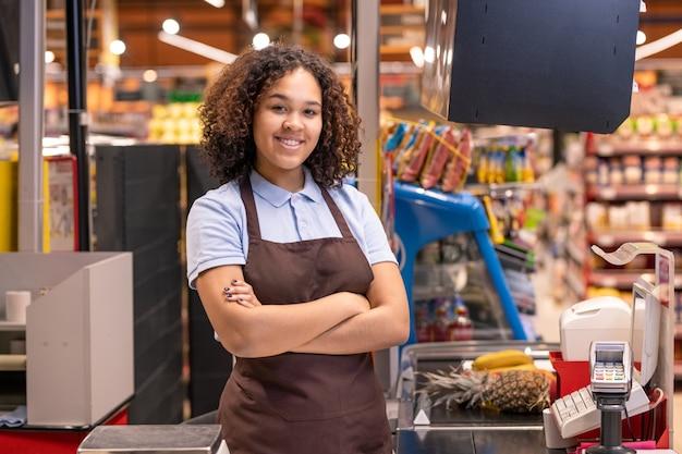 Linda mulher de avental parada junto à caixa de dinheiro no supermercado e cruzando os braços na parede das prateleiras com produtos alimentícios