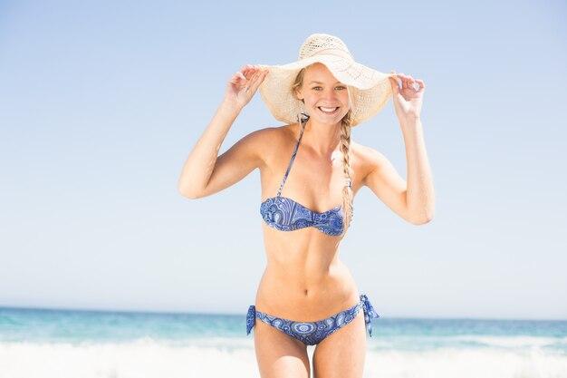Linda mulher de biquíni e praia chapéu em pé na praia