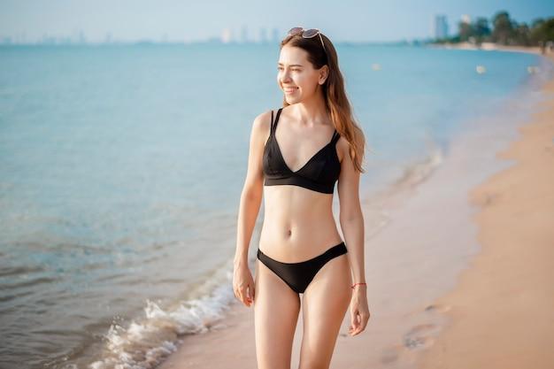 Linda mulher de biquíni preto está andando na praia