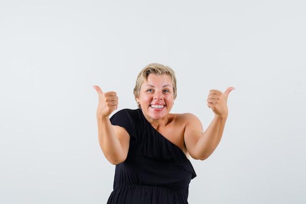 Linda mulher de blusa preta aparecendo o polegar e parecendo feliz