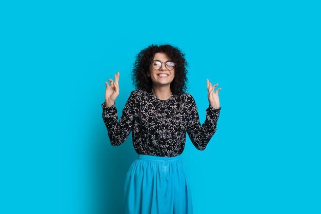 Linda mulher de cabelo encaracolado com óculos apontando para cima com as duas mãos enquanto posa