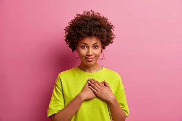 Linda mulher de cabelo encaracolado pressiona as palmas das mãos no peito, faz gesto de gratidão, obrigado por ajuda ou elogio, agradecendo, vestido com uma camiseta casual
