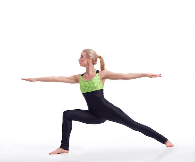 Linda mulher de cabelo loiro ajuste realizando asana guerreiro ioga