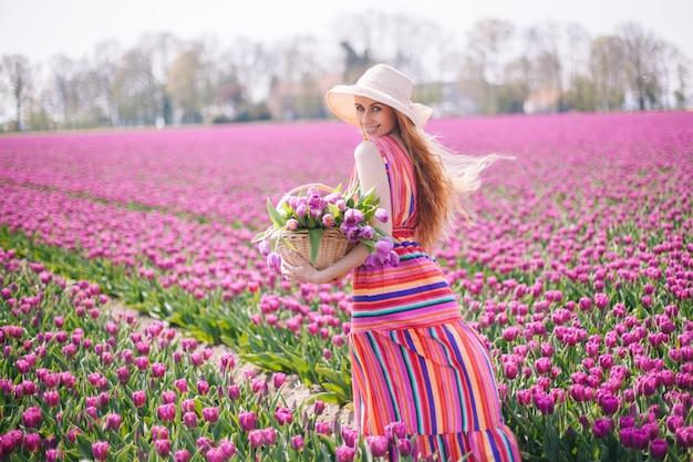 Linda mulher de cabelo vermelho, vestido listrado e segurando o buquê de flores tulipas na cesta