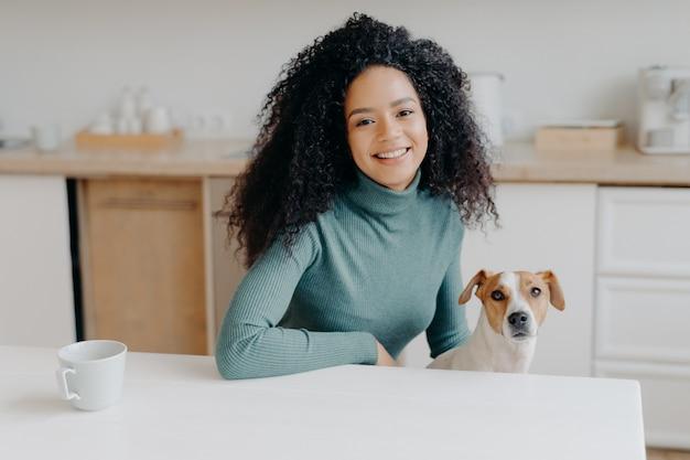 Linda mulher de cabelos cacheados vestida de gola alta casual, senta-se à mesa branca na cozinha, bebe chá da xícara, brinca com cachorro