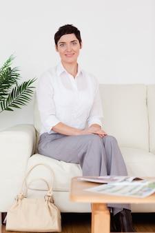 Linda mulher de cabelos curtos sentada em um sofá