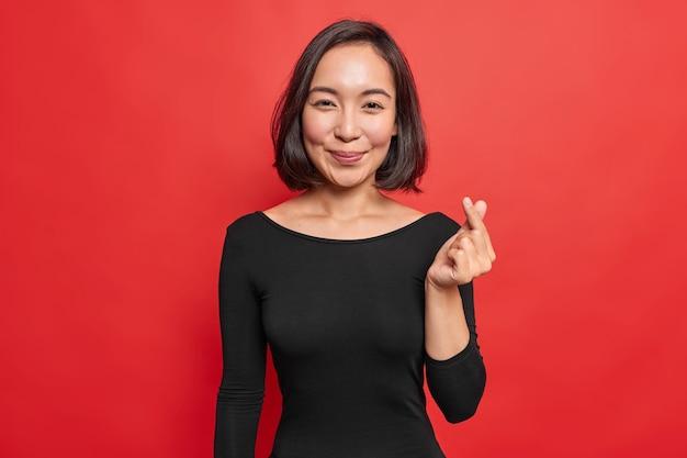 Linda mulher de cabelos escuros com aparência oriental que faz o sinal coreano expressar amor, tem sorrisos de clima romântico delicadamente vestida em poses de vestido preto contra uma parede vermelha vívida