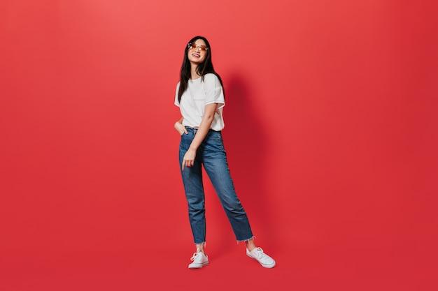 Linda mulher de cabelos escuros em jeans soltos e camiseta branca posando na parede vermelha