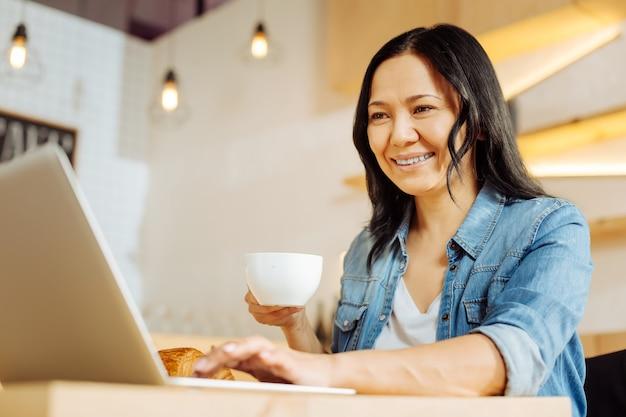 Linda mulher de cabelos escuros sorrindo e segurando uma xícara de chá e trabalhando em seu laptop