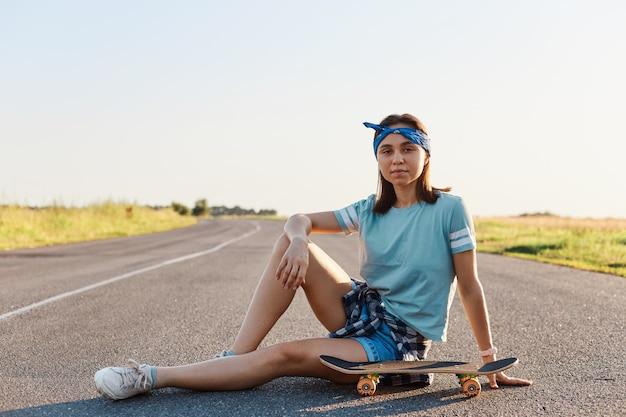 Linda mulher de cabelos escuros vestindo camiseta, short e sapatos sentado perto de skate de surf na estrada de asfalto ao ar livre, relaxe e desfrute de surfskate extremo no verão.