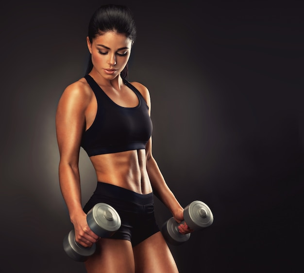Linda mulher de cabelos negros com corpo bem formado levantando halteres, mulher esportiva mostrando seu corpo bem treinado fitness, treinamento esportivo e estilo de vida saudável