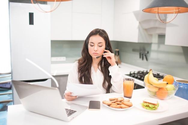 Linda mulher de cabelos pretos trabalha em casa e usa fones de ouvido com um fone de ouvido. um funcionário senta-se na cozinha e trabalha muito em um laptop e tablet, além de realizar videoconferência e reuniões.