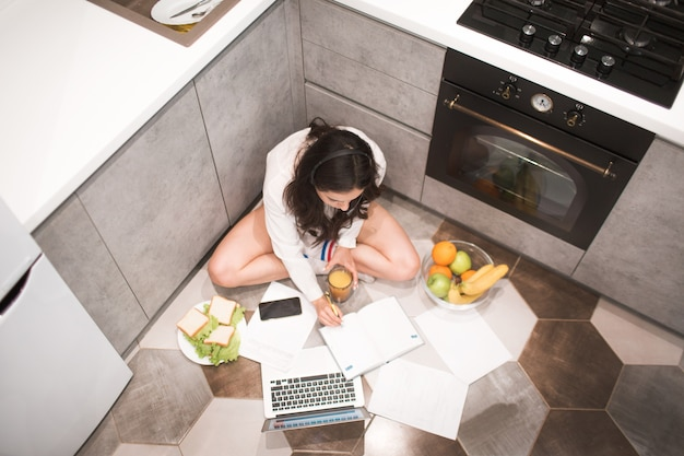 Linda mulher de cabelos pretos trabalha em casa. um funcionário senta-se na cozinha e trabalha muito em um laptop e tablet, além de realizar videoconferência e reuniões.