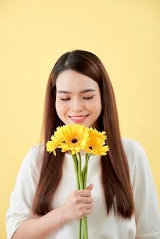 Linda mulher de camisa branca com flores gerbera nas mãos sobre um fundo amarelo. ela sorri e ri