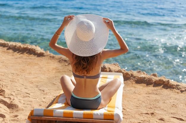 Linda mulher de chapéu branco e biquíni sentado numa espreguiçadeira perto do mar, na praia no egito. viagem de conceito de férias de verão