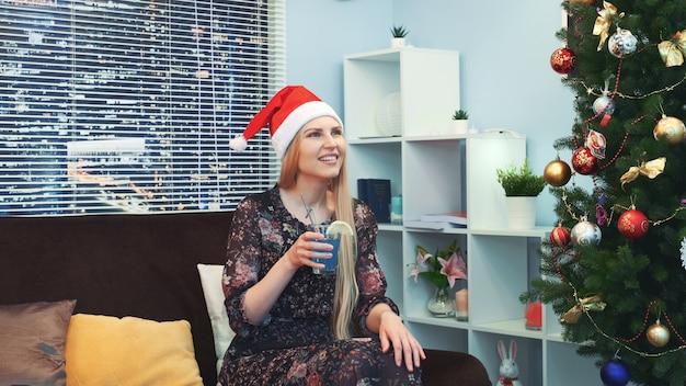 Linda mulher de chapéu de papai noel está esperando e comemorando emocionalmente a vinda de ano novo