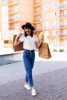 Linda mulher de chapéu e óculos de sol com sacolas de compras e sorvete falando na rua da cidade